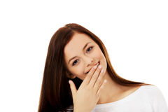 Young woman giggles covering her mouth with hand Stock Photos
