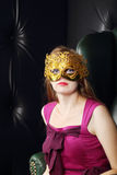 Young woman in gilt mask sits in leather armchair. In room with leather wall stock photos