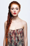 Young woman with ginger braids hairdo on white background. Young ginger woman with red braids hairdo on white background royalty free stock photos