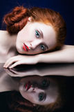 Young woman with ginger hair over reflection mirror on blue back. Beautiful young woman with ginger hair  over reflection mirror on blue background Royalty Free Stock Photos