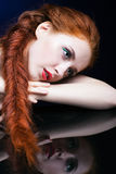Young woman with ginger hair over reflection mirror on blue back. Beautiful young woman with ginger hair  over reflection mirror on blue background Royalty Free Stock Images