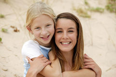 Young woman and girl at the beach. Portrait of a mother and daughter at the beach Royalty Free Stock Photos