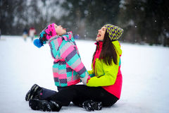 Young woman and the girl in bright ski suits sit having embraced on snow. Stock Photos