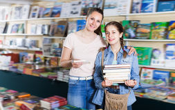 Young woman with girl buying books Stock Photography