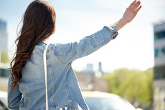 Young woman or girl catching taxi on city street Royalty Free Stock Image