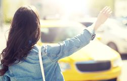 Young woman or girl catching taxi on city street stock images