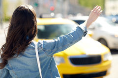 Young woman or girl catching taxi on city street Stock Image