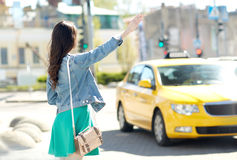 Young woman or girl catching taxi on city street stock photography