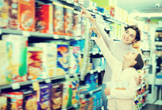 Young woman with girl choosing breakfast cereal royalty free stock photos