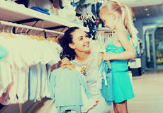 Young woman and girl in clothes store. Cheerful smiling young women with little daughter selecting blue kids apparel in clothes store Royalty Free Stock Photos