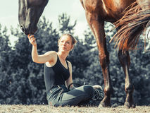 Young woman girl feeding horse. Stock Photo
