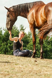 Young woman girl feeding horse. Young woman girl feeding and taking care of brown horse. Female with animal outdoor royalty free stock image