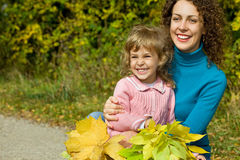 Young woman and girl laugh with leaves in garden Stock Image