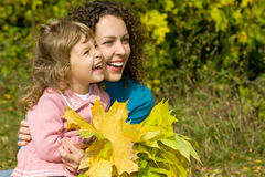 Young woman and girl laugh with leaves in garden. Young woman and little girl laugh with leaves in hands in garden autumn Stock Images