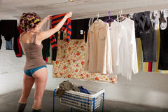 Girl stretches the clothes in the room. Young woman, girl in laundry Stock Images