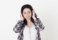 Young woman or girl listening to her favorite song closed eyes and holding big headphones with hands. She enjoys good music and pl Stock Photos