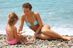 Young woman with girl played starfish on beach. Young woman with little girl played starfish on stony beach Royalty Free Stock Photography