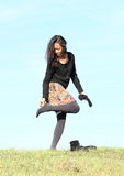 Young woman - girl putting on shoes on meadow Stock Photography