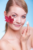 Young woman girl with red maple leaf and cream Stock Photography