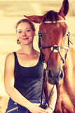 Young woman girl in stable with horse. Royalty Free Stock Image