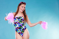 Young woman girl in swimsuit with pom poms. Gorgeous young woman girl in swimsuit swimwear with pom poms on blue. Summer holiday vacation relax Stock Photography