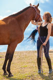 Young woman girl taking care of horse. Stock Photography