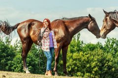 Young woman girl taking care of horse. Royalty Free Stock Image