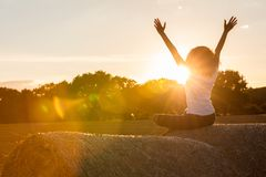 Young Woman Girl Teenager Sitting on Hay Bale Celebrating Sunset Royalty Free Stock Image