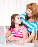 Young woman with girl using laptop computer Royalty Free Stock Images