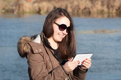 Young woman / girl using tablet outdoor sitting on bench near by. River and smiling; Girl using digital tablet pc in the park; Student using tablet after school Royalty Free Stock Images