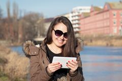 Young woman / girl using tablet outdoor sitting on bench near by. River and smiling; Girl using digital tablet pc in the park; Student using tablet after school Stock Photography