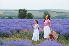 Young woman and girl are walking through the lavender flower field, beautiful summer landscape royalty free stock photo