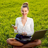 Young woman, girl working with laptop, tablet and phone in green Stock Photo