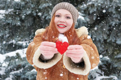 Young woman give red heart toy. Winter season. Outdoor portrait in park. Snowy weather. Valentine concept. Royalty Free Stock Images