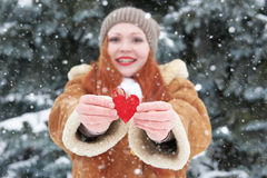 Young woman give red heart toy. Winter season. Outdoor portrait in park. Snowy weather. Valentine concept. Stock Image