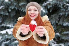 Young woman give red heart toy. Winter season. Outdoor portrait in park. Snowy weather. Valentine concept. Royalty Free Stock Photo