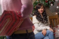 Young woman is given a gift for Christmas. A young woman is given a gift for Christmas Royalty Free Stock Images