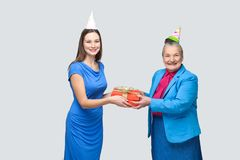 Young woman gives a gift to old funny woman for birthday Royalty Free Stock Photo