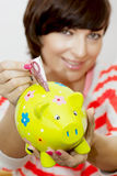 Young woman gives money to decorative ceramic piggy bank Royalty Free Stock Photo