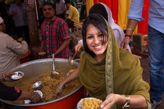 Young woman giving away rice at Guru Nanak Gurpurab celebration, Royalty Free Stock Images