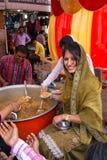 Young woman giving away rice at Guru Nanak Gurpurab celebration, Royalty Free Stock Image