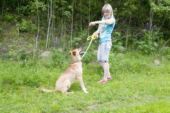 Young woman giving commands to her dog while walking on beach. Young woman giving commands to her dog while walking on the forest Royalty Free Stock Photos