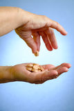 Young woman giving elderly woman pills Stock Photos