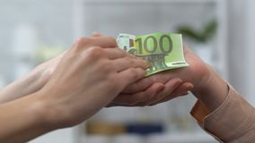 Young woman giving euro banknotes to retired female, donating money, charity. Stock footage stock video footage