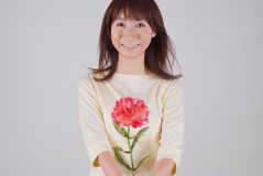 Young woman giving flower. Young Asian woman giving carnation flower Royalty Free Stock Photography