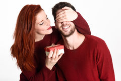 Young woman giving a gift to his man. Young women giving a gift to his man. Beautiful couple dressed in red on white background. Redhead girl Stock Image