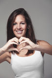 Young woman giving a heart gesture Royalty Free Stock Photo