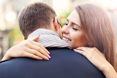 Young woman giving hug to her man. Picture showing happy couple hugging in the city stock photos