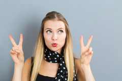 Young woman giving the peace sign Stock Photo