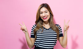 Young woman giving the peace sign Royalty Free Stock Photography